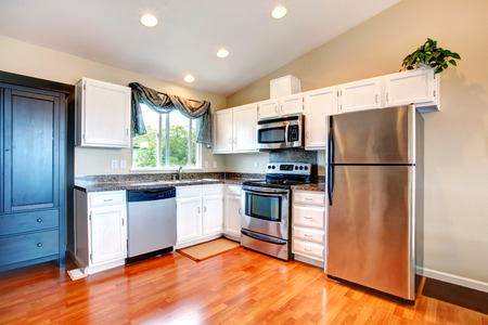 kitchen cabinets: Kitchen room with white cabinets and steel appliances