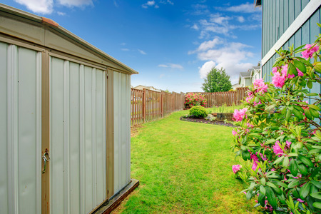 fenced: Fenced backyard with green lawn with blooming flowers  View of shed