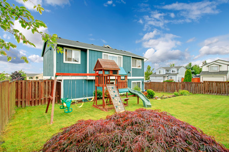 fenced: Small fenced backyard with playground for kids with chute, swings and climbing board