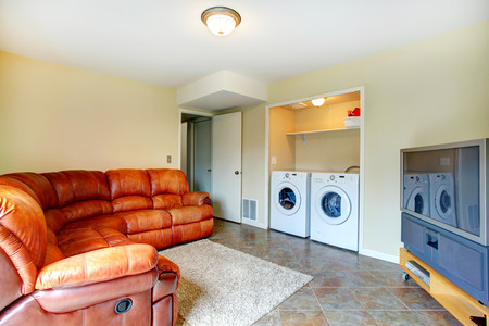 laundry room: Bright small living room with brown leather couch, tv and cabinet  Room has a built-in laundry area with washer and dryer
