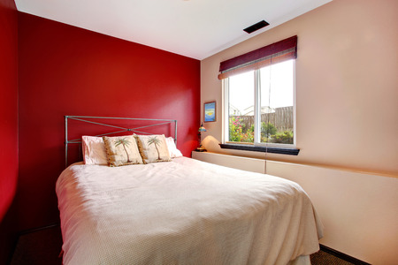 bedroom: Small bedroom with red and cream wall  Iron frame bed with tropical theme bedding Stock Photo