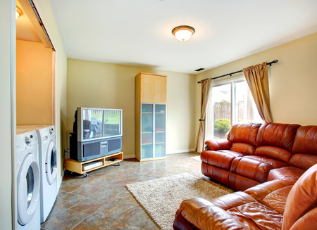 Bright small living room with brown leather couch, tv and cabinet  Room has a built-in laundry area with washer and dryer Stock Photo - 27594141