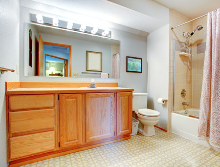 Bathroom with wooden vanity, bath tub with tile wall trim and light pink curtain photo