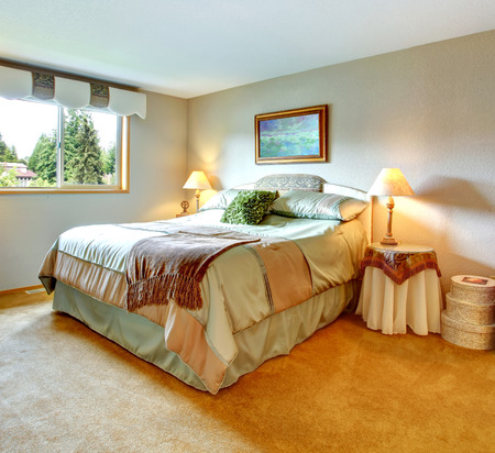 nightstands: Spacious bedroom with one window and carpet floor. Furnished with queen size bed, round nightstands and wooden dressers