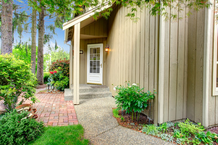 house siding: Wood siding house with small entrance porch. View of white french door and walkway Stock Photo