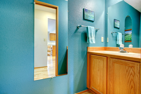 Bathroom corner. View of wooden washbasin cabinet and turquoise wall with mirror