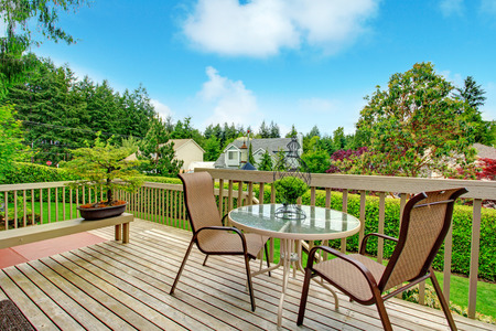 round chairs: Cozy wooden deck with glass top round table and chairs