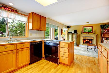 black appliances: Camera Cucina con armadi in legno e elettrodomestici neri. Vista da soggiorno con camino