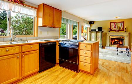black appliances: Camera Cucina con armadi in legno e elettrodomestici neri. Vista del soggiorno con camino Archivio Fotografico