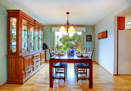 Open dining area with served table and cabinet. Stock Photo - 27659041