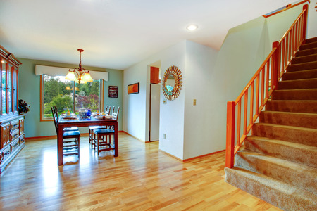 Open dining area with served table and cabinet. View of staircase Stock Photo - 27659042
