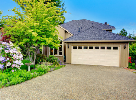 driveways: House exterior. View of garage with driveway and beautiful green flower bed