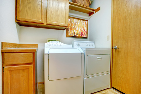 Small laundry room with wooden cabinets, and white appliances photo