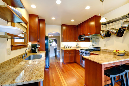 Practical kitchen room interior  Cabinets, steel appliances, hanging pot rack  Kitchen room has a dining area photo