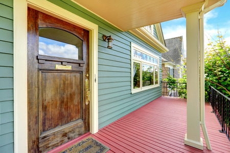 welcome door: Entrance column porch with red wooden floor and iron railings  View of door with welcome rug