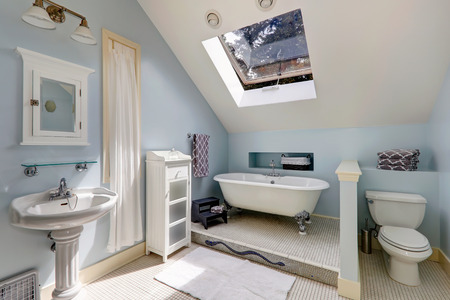 bathroom interior: Light blue velux bathroom with window  View of white antique freestanding bath tub, washbasin stand and toilet