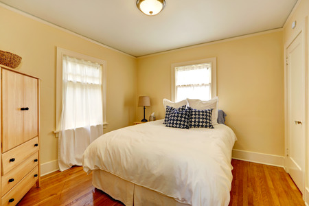 bedroom furniture: Small cozy bedroom with bed and wooden dresser  Room has two windows and hardwood floor