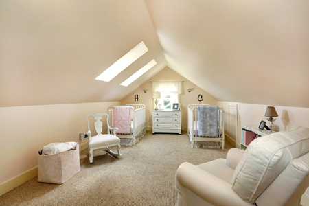 Ivory vaulted ceiling nursery room with two cribs, rocking chair and armchair  Room has two velux windows photo