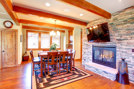 Dining room interior  Celing beams blend perfectly with stone wall trim and fireplace  Dining room has wooden table set and tv photo