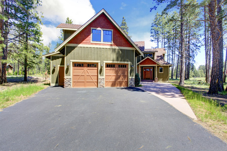 two car garage: Big luxury house with green and orange siding trim  View of entrance porch and two car garage