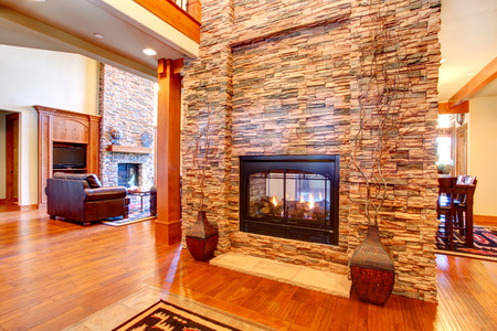 fireplace: Beautiful stone wall with built-in fake fireplace  Two vases with dry branches complete the wall look