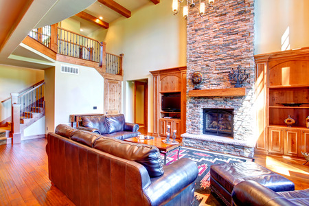 Luxury living room with stone wall trim and fireplace  Room furnished with rich leather furniture set and coffee table
