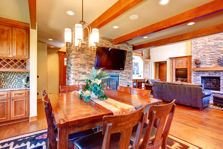 Dining room interior  Ceiling beams blend perfectly with stone wall trim and fireplace  Dining room has wooden table set and tv photo