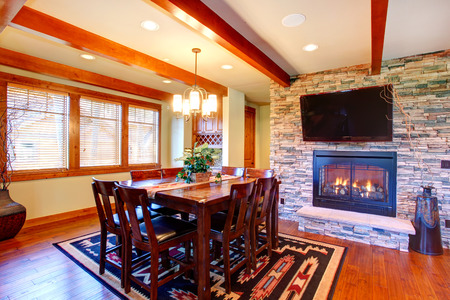 stone fireplace: Dining room interior  Ceiling beams blend perfectly with stone wall trim and fireplace  Dining room has wooden table set and tv