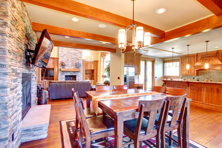 ceiling texture: Dining room interior  Ceiling beams blend perfectly with stone wall trim and fireplace  Dining room has wooden table set and tv  View of kitchen and living room