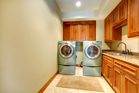 Rectangle laundry room with wooden cabinets and modern shiny appliances photo