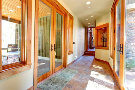 niche: Long entrance hallway with glass doors. View of niche in the wall decorated with dry branches Stock Photo