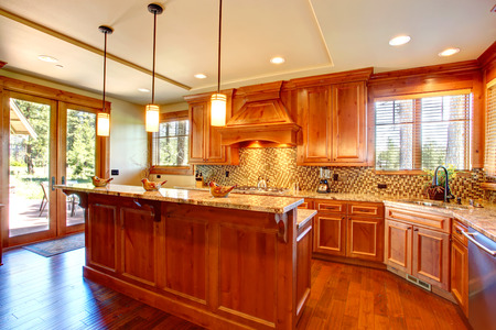 back kitchen: Spacious kitchen room with honey cabinets, back splash trim and kitchen island. Room has door to the backyard deck