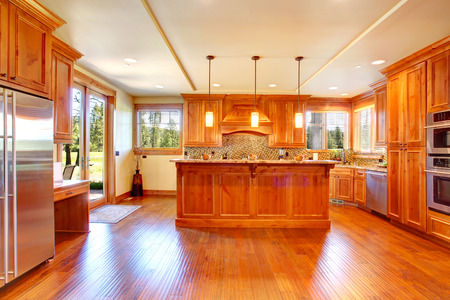 Spacious kitchen room with honey cabinets, back splash trim and kitchen island. Room has door to the backyard deck photo