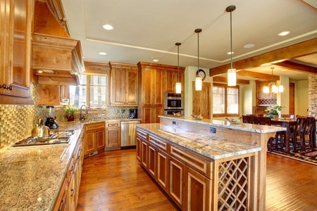 Spacious kitchen room with honey cabinets, back splash trim and kitchen island. Room has dining area Stock Photo