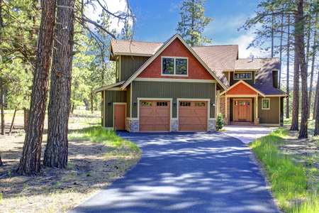 two car garage: Big luxury house with green and orange siding trim. View of entrance porch and two car garage Stock Photo