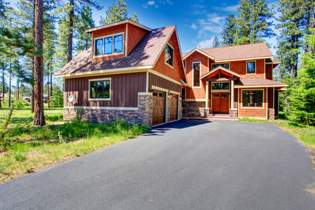 two car garage: Big luxury house with brown and orange siding trim. View of entrance porch and two car garage