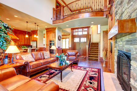 stone  fireplace: Luxury living room with stone wall trim and fireplace  Room furnished with rich leather furniture set and coffee table  View of balcony loft