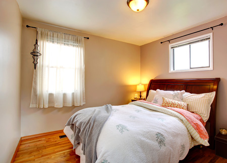 Small bedroom with queen size bed and refreshing bedding Reklamní fotografie