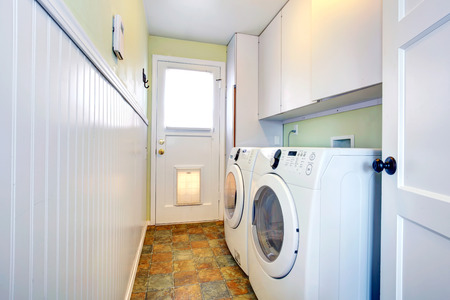 Narrow small laundry room with white cabinets and white modern appliances photo