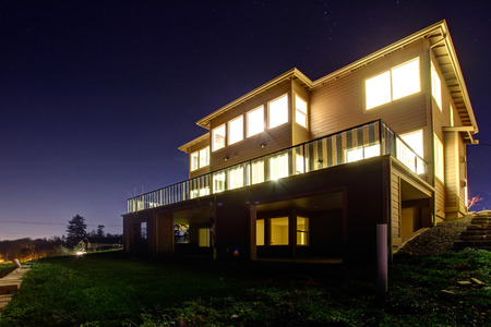 Big modern house with bright lights on in windows on a beautitul summer evening photo
