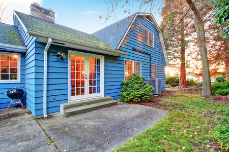 french doors: Blue clapboard siding house with white french door  Backyard view Stock Photo