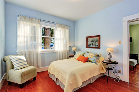 nightstand: Light blue bedroom with window and hardwood floor furnished with bed and chair