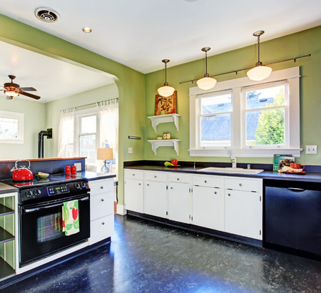 black appliances: Kitchen room with green walls, white cabinets and black appliances