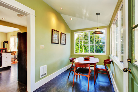 Small green dining area with table set and french window, photo