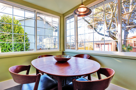 Small green dining area with table set and french window photo
