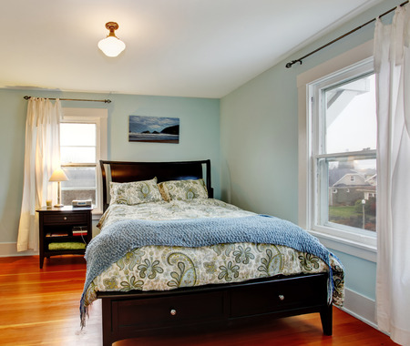 Lgiht blue bedroom with two windows and hardwood floor. Furnished with black furniture set photo