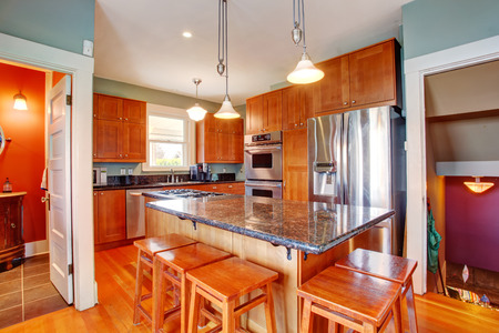 Kitchen storage combination with steel appliances and island in the center of the room Stock Photo - 28130366