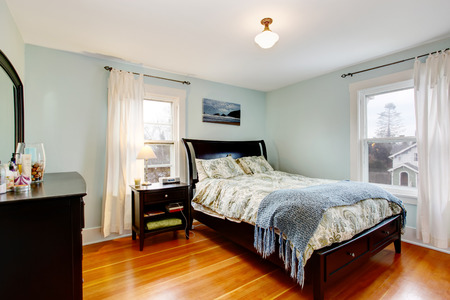 furniture: Lgiht blue bedroom with two windows and hardwood floor  Furnished with black furniture set