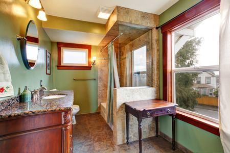Green bathroom with tile floor and tile wall trim behind tub Stock Photo - 28130377