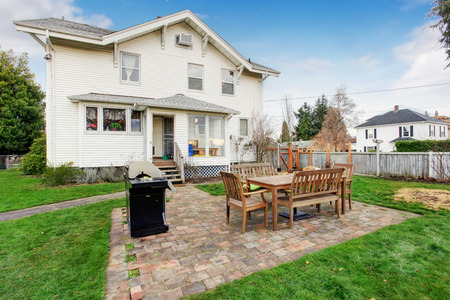 fenced: Fenced backyard with small patio area  View of wooden table set and barbecue